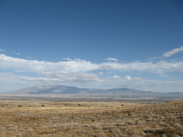 The Sandia ranging above Albuquerque and orange green band of the river running through it
